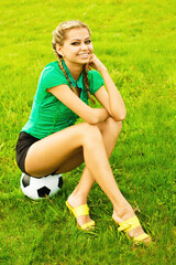 Beautiful girl with a classical soccer ball sitting on the grass