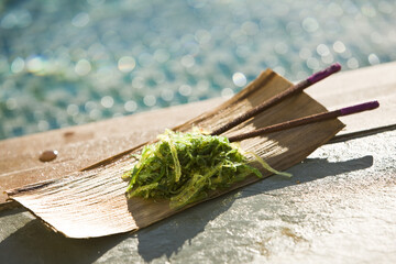 Close-up of seaweed with chopsticks on a wooden tray at the poolside