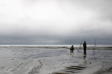 two fisherman on the beach