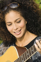 Woman playing a guitar and smiling