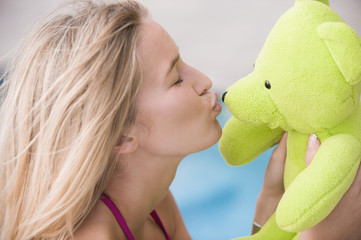 Close-up of a woman kissing a teddy bear