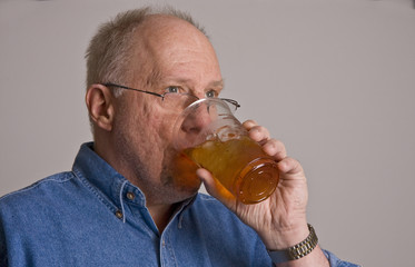 Older Man Drinking Iced Tea From Plastic Cup