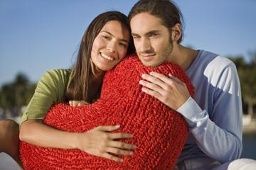 Portrait of a couple hugging a heart shaped cushion