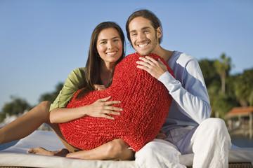 Portrait of a couple holding a heart shaped cushion