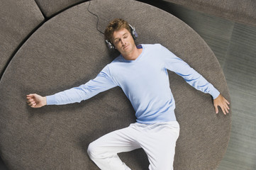 Man lying on a round sofa and listening to music