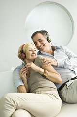 Couple listening to music with headphones and smiling