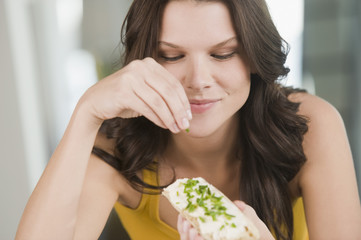 Woman sprinkling chive on a bread and smiling