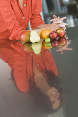Reflection of a woman and fruits on a kitchen counter