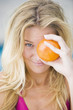 Close-up of a woman holding an orange in front of her eye
