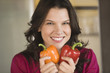 Woman holding an orange and a red bell pepper