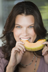 Portrait of a woman biting a slice of cantaloupe