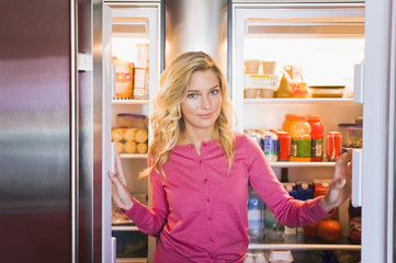 Portrait of a woman standing in front of a refrigerator