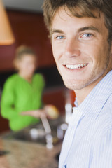 Portrait of a man smiling with a woman washing vegetable in the background