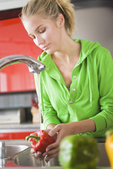 Close-up of a woman washing bell peppers under a faucet