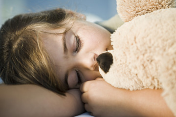 Close-up of a girl sleeping with a teddy bear