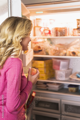 Close-up of a woman opening refrigerator in the kitchen