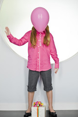 Pink balloon tied with a birthday present in front of a girl's face
