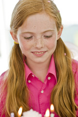 Close-up of a girl looking at a birthday cake