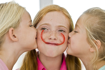 Close-up of two girls kissing their friend