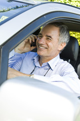 Man in a car and talking on a mobile phone