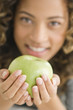 Portrait of a girl holding a green apple and smiling