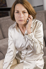 Woman talking on a mobile phone and looking serious