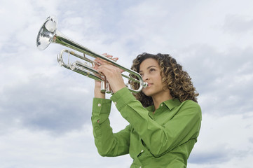 Low angle view of a girl playing a trumpet