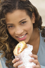 Portrait of a girl holding a sandwich and smiling