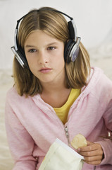 Girl listening to headphones and holding potato chips