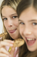 Two girls eating chocolate cookies