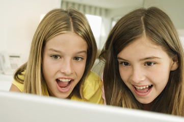 Two girls looking at a laptop with surprise