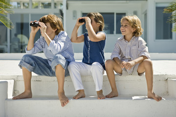 Two children looking through binoculars with their friend sitting beside them