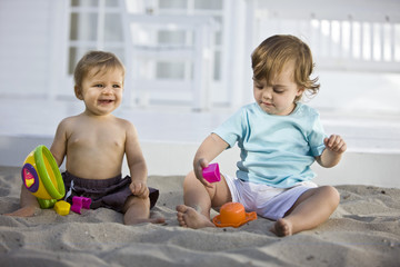 Two babies playing with toys in sand