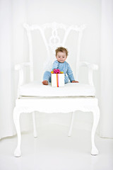 Baby boy sitting in an armchair with a gift