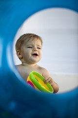 Baby boy playing with a toy viewed through an inflatable ring
