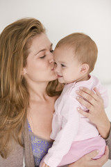 Woman kissing her daughter