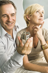 Man looking at a model home with her wife thinking beside him