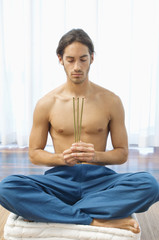 Man practicing yoga and holding incense sticks