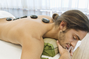 Man receiving hot stone therapy
