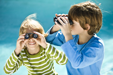 Two boys looking through binoculars