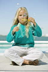Girl blowing soap bubbles with a bubble wand