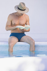 Man reading a book at the poolside