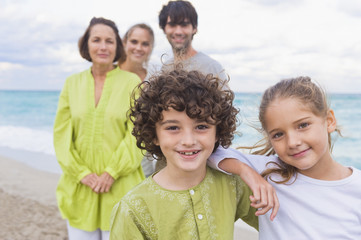 Boy and a girl smiling with their family behind them on the beach