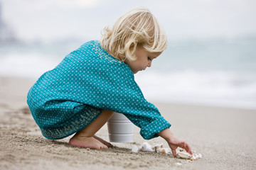 Girl playing with shells on the beach