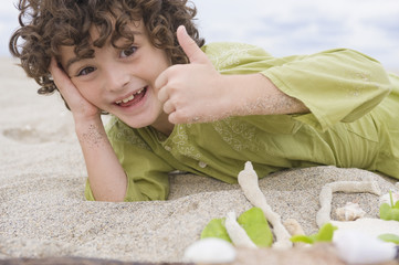 Boy showing thumbs up sign on the beach