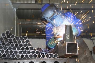 Man welding pipes on a production line
