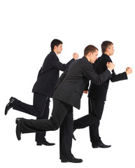 Three young businessmen run, side view