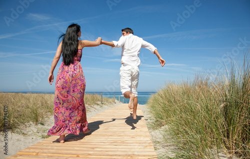 love couple running with holding hands to the beach