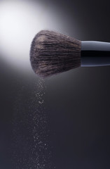 Makeup brush with spilling face powder on dark background