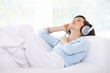 Woman is listen to the music on couch